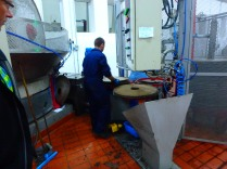 Working the crushed pulp before it gets pressed on those round things.