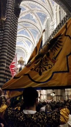 Aquila contrada flag bearer during mass inside the Duomo