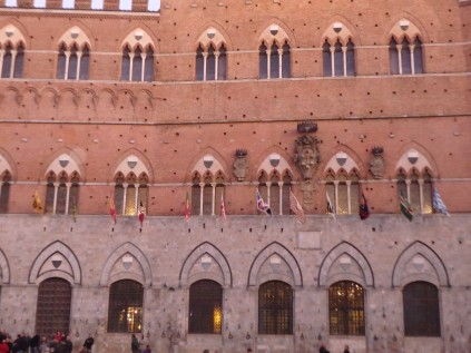 The march starts in the Piazza del Campo. The flags represent each contrada.