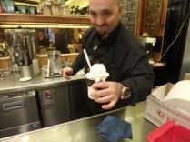 A barista handing me my granita' di caffe' con panna at Tazza d'Oro.