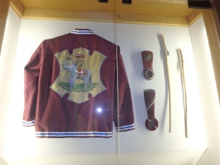 Jacket of the fantino, or rider, of the Torre, the contrada markers that are clipped to the horse bridles in case the rider falls off and the horse finishes and the whips, or nerbi, given to the rider.