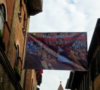A poster of the Torre's winning fantino from July 2 Palio right the moment of victory, strung across the street. How great is this?