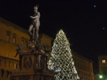 The Neptune fountain in Piazza Maggiore next to Bologna's beautiful Christmas treet.