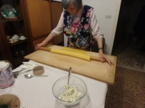 Maria continues to spread out the dough. She's a pro. The bowl with the ricotta filling is the foreground.