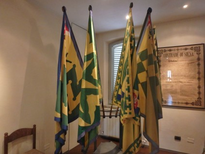 Il Bruco flags inside the contrada headquarters