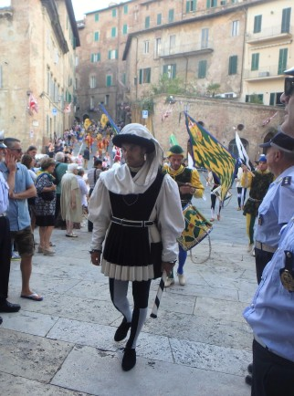 The march of the contrade into the church of Santa Maria in Provenzano, the patron of the July 2 Palio. The Palio banner is blessed here in a short ceremony.