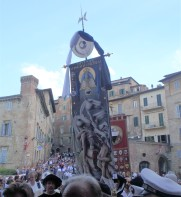 The Palio banner being carried into the church of Santa Maria in Provenzano. This is the prize for the winner of the Palio.
