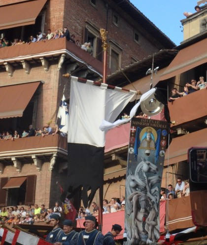 The Palio banner makes its way around the Piazza. Contrada members wave their fazzoletti as it passes them.