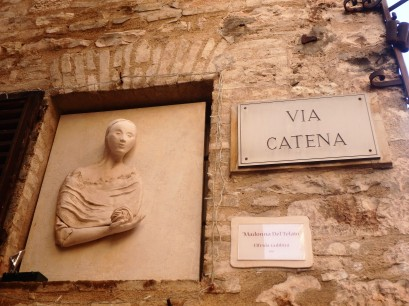 "This is a terracotta sculpture by artist Elfrida Gubbini, called ""La Madonna Del Telaio."" She made it for Paola Tacconi, who owns the clothing store, La Bottega degli Intrecci. The name means ""Madonna of the Loom"" and is on the wall outside of the shop."