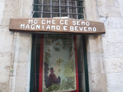 "Translation: ""GIA' CHE CI SIAMO, MANGIAMO E BEVIAMO"" a Romanesco dialect. Which means ""We're here, eating and drinking."" (Sounds better in Italian.)"