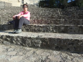 Sitting in the Roman ampitheater. Yes, that's me.