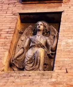 The angel on the facade of the Duomo. There are four statues on the facade - angel, lion, bull and eagle. (aquila in italian). Take the first letter of each: ALBA