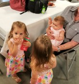 Quinn, left, and her twin sister Nora, discussing something very important with baby Evelyn.