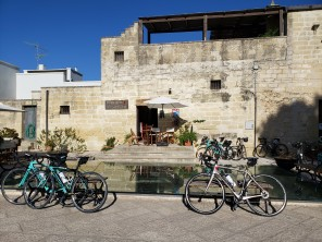 Our bikes in front of the covered ancient wells in the piazza in Acaya (photo: Melanie F)
