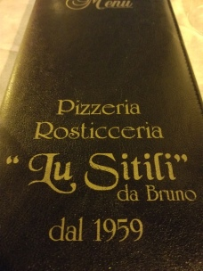 "The locale for the pizzeria is in a piazza called ""Lu Sitili'"