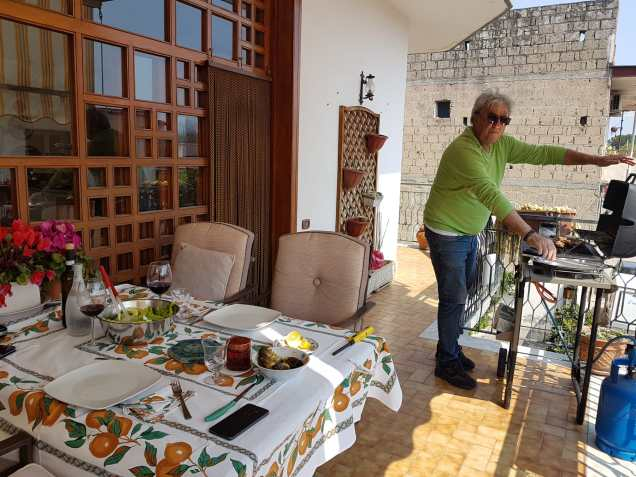 Antonio at the grill on their balcony next to the dinner table. What a nice day!