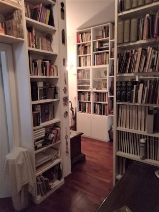 Inside Paola's apartment where her big project is to go through her books and decide which ones to donate. She's not having much luck.